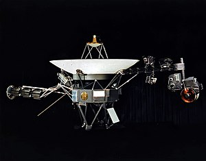 A space probe resting on a stand, with a parabolic antenna pointing upwards and two arms extending from the sides, bearing cameras and other devices, against a black background curtain