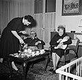 Vrouw bij het koffie inschenken voor de visite terwijl een dame de baby op schoo, Bestanddeelnr 252-9372.jpg