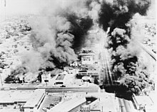 Several buildings burning in an aerial black and white photograph.