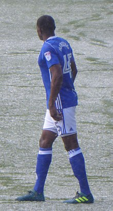 Black-skinned man in football kit on a snowy pitch