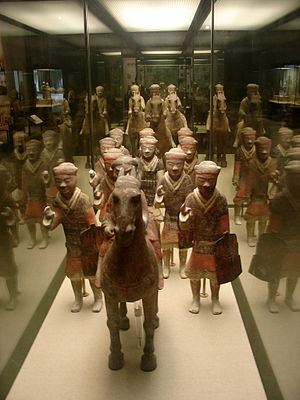 Red Eyebrows - Painted ceramic statues of one Chinese cavalryman and ten infantrymen with armor, shields, and missing weapons in the foreground, and three more cavalrymen in the rear, from the tomb of Emperor Jing of Han (r. 157 - 141 BC), now located at the Hainan Provincial Museum