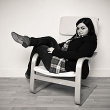 A Woman Lounging In A Poäng Chair