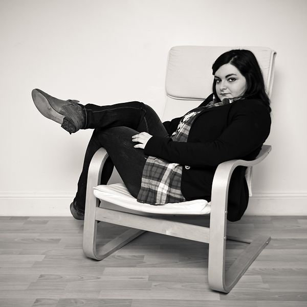 Woman lounging in an IKEA Poäng chair