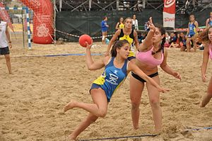 Beach handball - A female player dashes to score a point