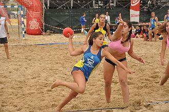 Beach handball - A female player dashes to score a point