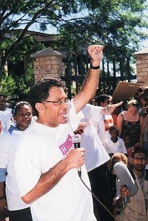 "Zackie Achmat - Achmat speaking at a protest wearing the TAC's trademark ""HIV Positive"" T-shirt"