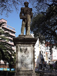Photograph depicting an urban square, in the center of which is a stone plinth on which is a bronze statue depicting a bearded man in military dress uniform whose right hand holds a bicorn hat