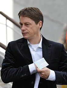 The upper body of a middle-aged white man with brown hair. He is wearing a light-coloured shirt with light blue pinstripes over a white T-shirt with a dark jacket on top. His right hand is inside his jacket and his left hand is holding a piece of paper.