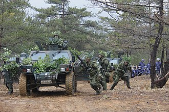 Maneuver warfare - JGSDF soldiers rush out of their LAV to counter an ambush.