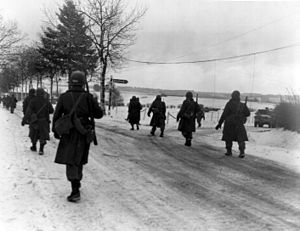 Troops of the 101st Airborne move out of Bastogne, after having been besieged there for ten days, December 31, 1944. 101st Airborne troops move out of Bastogne.jpg