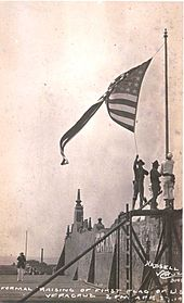 photograph of a walled fort with three Marines raising a U.S. flag over it