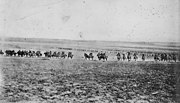Mounted soldiers charge towards the camera over rocky ground