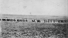 A line of men on horses charge across an open field towards the camera