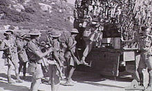 Soldiers in tropical uniforms climb on to a truck