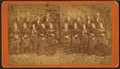 A group portrait of 9 unidentified men and women pose in front of a painted backdrop, by Tuttle, W. C. (William C.).png