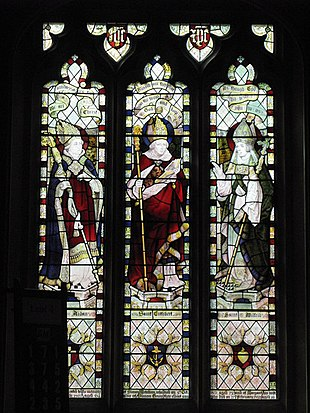 Three stained glass windows, each depciting a mitred and robed figure. All three are carrying staves.