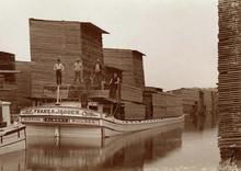 Um barco chato com grandes tábuas de madeira empilhadas flutua em um canal estreito cercado por mais pilhas de tábuas de madeira.  Alguns homens posam no barco.