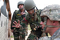An Indian Army soldier confirms the adjustment needed to the scope of his M4 carbine with a U.S. Army paratrooper.jpg