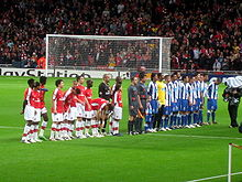 Two football teams and a refereeing team lining up in a football stadium pitch. The leftmost team wears red shirts and white shorts and socks, while the other wears blue shorts and socks and shirts with vertical blue-and-white stripes. The refereeing trio wears light gray equipment. A goal and a packed stand behind it are seen in the background.