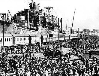 Soldats, au premier plan, attendant pour embarquer dans un train dans le fond, celui-ci se trouvant devant un navire.