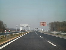 A view of motorway and a traffic sign indicating distances to tourist destinations