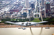B-2 in flight over the Mississippi River (St. Louis, Missouri) with the Gateway Arch and Busch Stadium in the background.