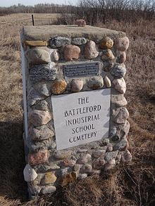 Stone cairn erected in 1975 marking the Battleford Industrial School Cemetery. A plaque at the top of the cairn reads: RESTORATION THROUGH OPPORTUNITIES FOR YOUTH, 4S1179-1974. PLAQUE PROVIDED BY DEPARTMENT OF TOURISM AND RENEWABLE RESOURCES.