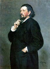 A middle-aged man with medium-length dark hair and a beard, wearing a dark suit, with one hand in his trouser pocket and the other hand on his chin.