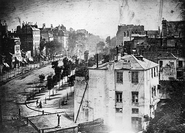 Boulevard du Temple, Paris, 3rd arrondissement, Daguerreotype. Made in 1838 by inventor Louis Daguerre, this is believed to be the earliest photograph showing a living person. It is a view of a busy street, but because the exposure lasted for several minutes the moving traffic left no trace. Only the two men near the bottom left corner, one apparently having his boots polished by the other, stayed in one place long enough to be visible. As with most daguerreotypes, the image is a mirror image.