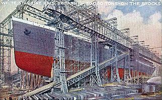 Grande casco de um navio em seu estaleiro, pintado de cinza acima da linha de água e vermelho abaixo