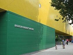 """Uma parede exterior verde está uma história de altura, e em cima dela, a parede é amarelo.  Na parte verde são as palavras """"crianças de Brooklyn do museu"""" na pia batismal de prata.  Alguns adultos e crianças estão na calçada em frente ao prédio."""