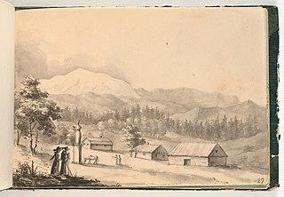 Bjerglandskab. I forgrunden tre lave huse samt en høj sokkel med en statue ved hvis fod græsser et æsel. Endvidere ses længst i forgrunden to samtalende mennesker, den ene med en stok i hånden