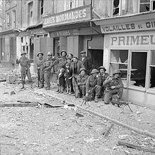 A mixed group of soldiers and civilians in front of some damaged shops; the street is littered with debris