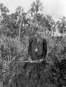 A black and white photograph of a Seminole man wearing traditional Seminole smock and vest, holding a rifle standing among palmettos, and staring at the viewer