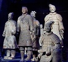 Photographie de six statues de soldats en terre cuite coiffés et vêtus distinctement, l'un assis au premier plan et les autres debout.