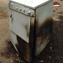 A photo of a clothes dryer that has been damaged by fire.