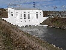Centrale électrique avec canal de fuite sortant de la base;  transformateurs électriques sur la rive du canal à droite