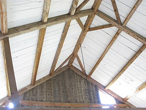 Purlin - A view of a roof using common purlin framing. This view is from the inside of the building, below the roof. The rafters are the beams of wood angled upward from the ground. They meet at the top of the gable at a ridge beam, which has extra bracing to attach it to the rafters.  The purlins are the large beams perpendicular to the rafters; from this shot, it appears that there are three purlins on either side of the roof. The sheathing boards are sometimes called the roof deck and are painted white.