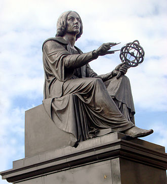 Nicolaus Copernicus Monument, Warsaw - Copernicus holds a compass and armillary sphere