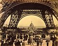 Crowd of people walking under the base of Eiffel Tower, view toward the Central Dome, Paris Exposition, 1889.jpg
