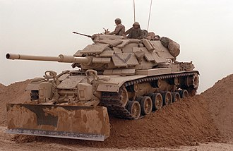 Liberation of Kuwait campaign - An American M60 Patton tank breaches the Iraqi defense line in Kuwait on 24 February..