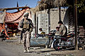 Defense.gov News Photo 111111-M-MM918-003 - U.S. Marine Lance Cpl. Kevin Jones walks past a group of Afghan citizens during a security patrol in the Garmsir district of Helmand province.jpg