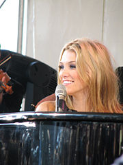 A blonde woman smiles as she looks to her right while sitting behind a piano