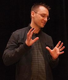 A man with short, spiked up hair stands with his hands up and a microphone clipped to his shirt
