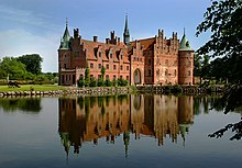 A large three-storied castle has  steeply pitched roofs,  two circular towers and a spire, and a large arched entrance facing a lake which reflects the castle's image.
