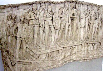 Auxilia - Roman auxiliary infantry crossing a river, probably the Danube, on a pontoon bridge during the emperor Trajan's Dacian Wars (AD 101–106). They can be distinguished by the oval shield (clipeus) they were equipped with, in contrast to the rectangular scutum carried by legionaries. Panel from Trajan's Column, Rome