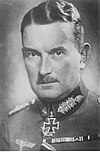 A man with mustache wearing a military uniform with an Iron Cross displayed at the front of his uniform collar.