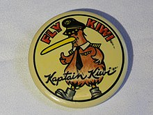 "Promotional button for Kiwi International Airlines, circa 1994. Diameter 54mm. Yellow background, with cartoon figure of a Kiwi bird wearing airline captain's hat, tie, wings, and shoulder insignia. Says ""FLY WIKI"" in red block letters on the top, and ""Kaptain Kiwi"" in script across the bottom."
