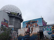 An empty building and geodesic dome at the listening station are covered with various murals and graffiti.