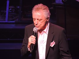 Valli singing into a microphone onstage